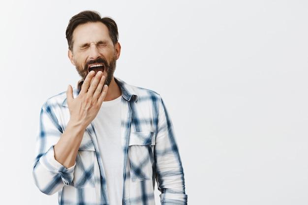 Homme d'âge mûr barbu fatigué posant