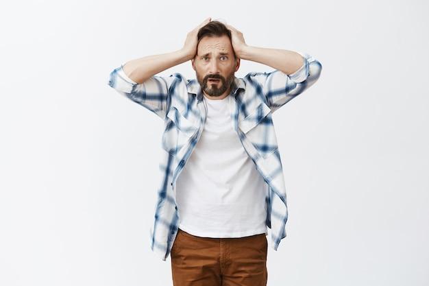 Homme d'âge mûr barbu inquiet et en détresse posant