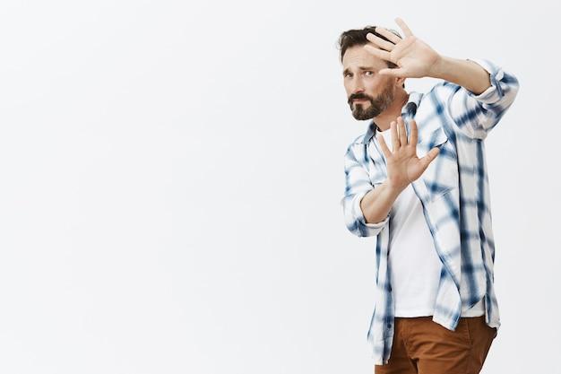 Homme d'âge mûr barbu insécurisé posant
