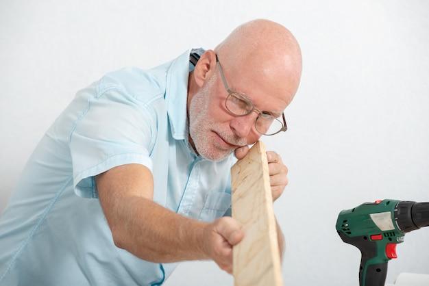 Homme d'âge mûr avec une chemise bleue, bricoleur à la maison