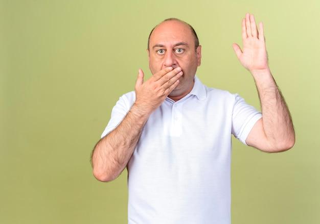 Homme d'âge mûr effrayé bouche couverte et main levée isolé sur mur vert olive