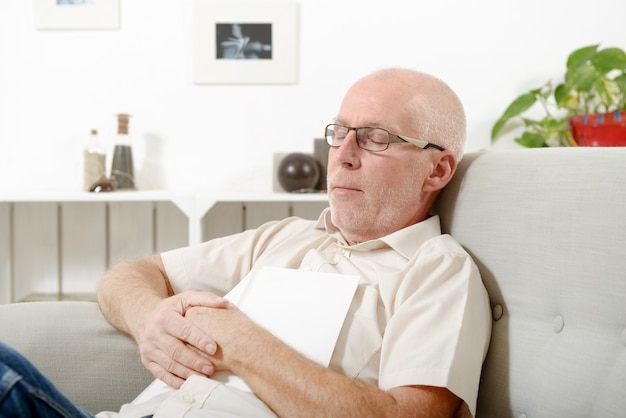 Homme d'âge mûr faisant une sieste dans un canapé à la maison