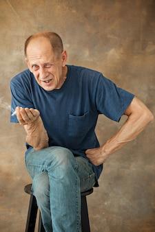 Homme d'âge mûr inquiet assis, fumer et penser à quelque chose
