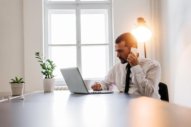 Homme d'âge mûr occupé en chemise et cravate travaillant sur un ordinateur portable et parlant au téléphone