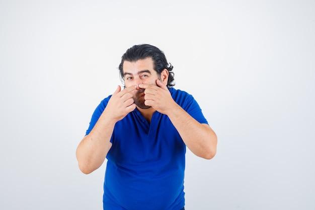 Homme d'âge mûr popping bouton en t-shirt bleu, jeans et à la recherche concentrée. vue de face.