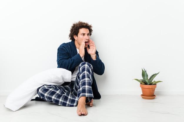 Un homme d'âge mûr portant un pyjama assis sur le sol de la maison crie fort, garde les yeux ouverts et les mains tendues.