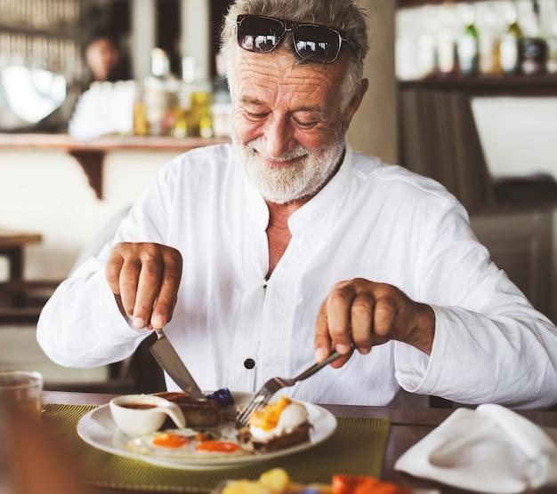 Homme d'âge mûr prenant son petit déjeuner à l'hôtel