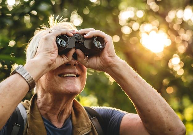 Homme d'âge mûr regardant des oiseaux à travers des jumelles