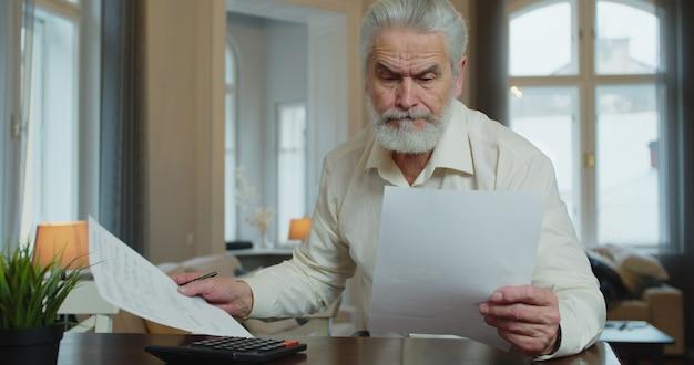 Homme d'âge mûr sérieux calcul des factures, vérification des finances gérer les finances personnelles assis à table à la maison.