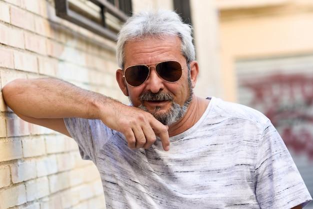 Homme d'âge mûr souriant avec des lunettes de soleil aviateur en milieu urbain