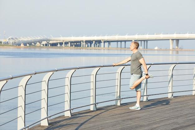 Homme d'âge mûr sportif tenant la balustrade et étirement de la jambe sur la rivière tout en se préparant à courir