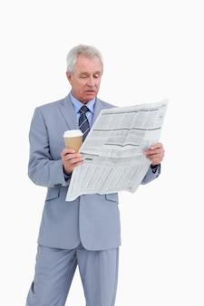 Homme d'âge mûr avec une tasse en papier, lisant un journal
