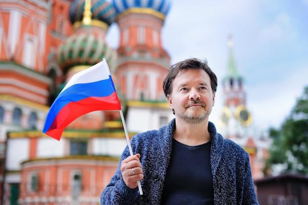 Homme d'âge mûr tenant un drapeau russe avec la cathédrale saint-basile