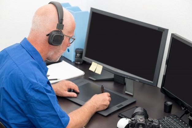 Homme d'âge mûr travaillant avec une tablette graphique dans son bureau