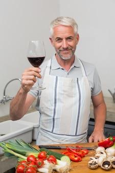 Homme d'âge mûr avec verre à vin en hachant les légumes dans la cuisine