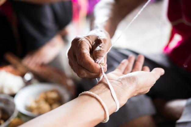 Un homme âgé non identifié appartenant à une minorité ethnique karen attache le poignet d'un invité pour lui avoir accordé sa bénédiction lors d'une cérémonie de ligage