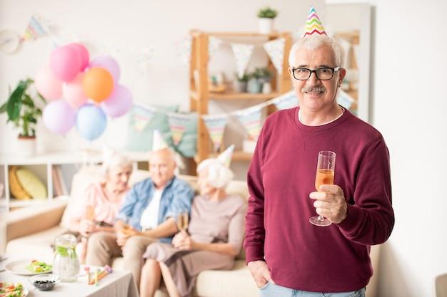 Homme âgé occasionnel avec flûte de champagne avec ses amis sur le canapé à la fête d'anniversaire