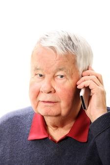 Un homme âgé parlant au téléphone sur fond blanc