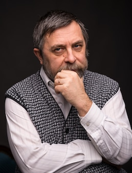 Homme âgé pensif qui pose en studio sur un fond sombre