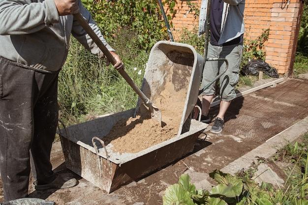 Un homme âgé pétrit du ciment pour verser un chemin de jardin, des travaux de construction de jardin.