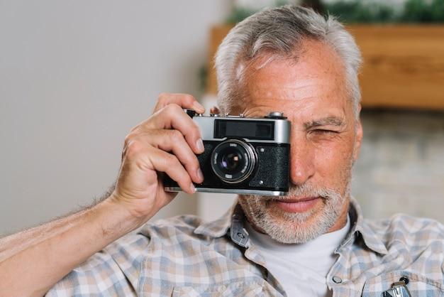 Un homme âgé prenant une photo de la caméra
