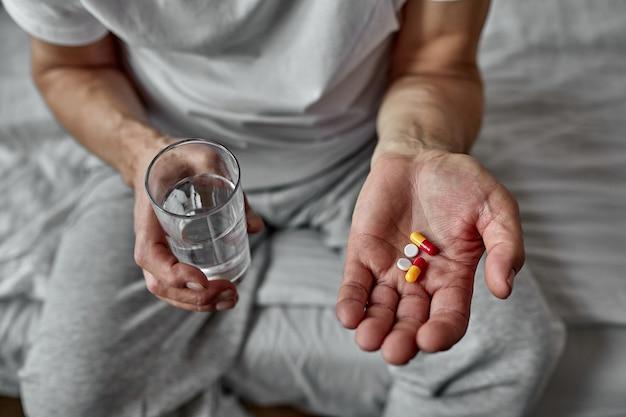 Homme âgé, prendre des pilules, gros plan. beaucoup de pilules dans les mains. prendre soin de la santé des personnes âgées. problèmes de santé à un âge avancé, prise de plusieurs médicaments.