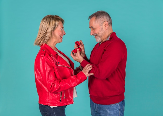 Homme âgé présentant une boîte à bijoux à une femme émerveillée