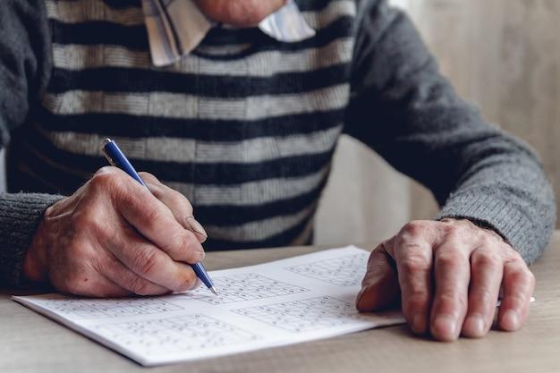 Un homme âgé résout le sudoku ou un jeu de mots croisés