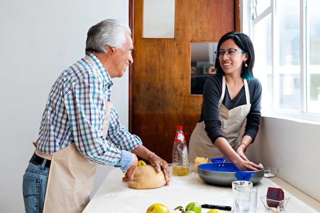 Un homme âgé et sa petite-fille préparent un bol et de la pâte pour cuire du pain dans une cuisine, tous deux portant des tabliers