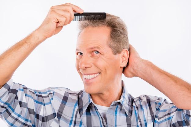 Homme âgé se peignant les cheveux