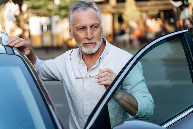 Un homme âgé se tient près de sa voiture suv de location et tient des lunettes de soleil. portrait d'homme d'âge moyen à l'extérieur près de sa voiture de location