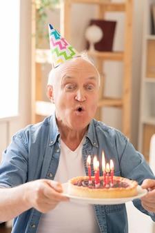 Homme âgé soufflant des bougies sur un gâteau d'anniversaire fait maison tout en célébrant seul