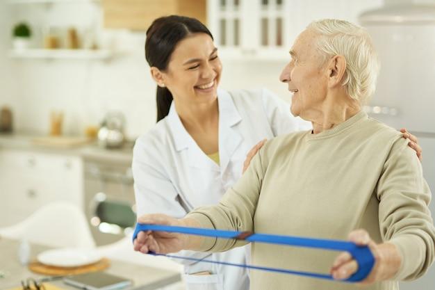 Homme âgé souriant et jeune infirmière se regardant
