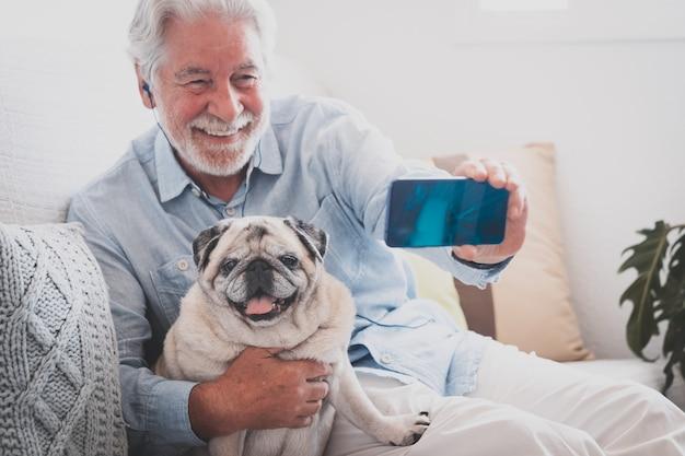 Un homme âgé souriant prend un selfie avec son meilleur ami, un chien carlin de race pure assis ensemble à la maison
