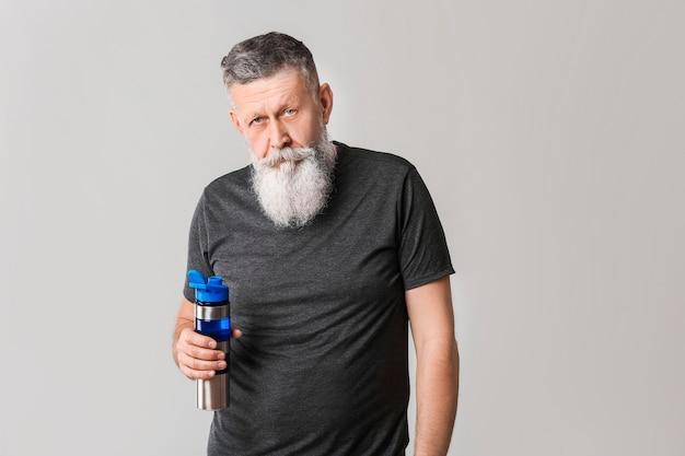 Homme âgé sportif avec une bouteille d'eau sur fond gris