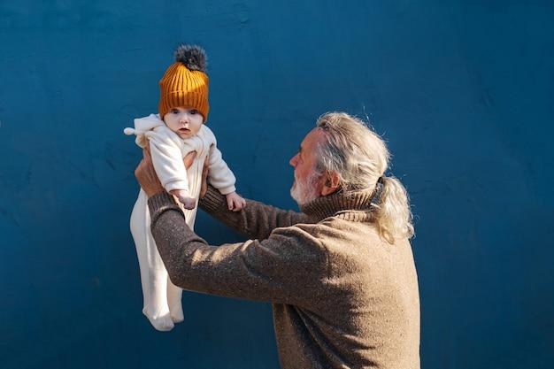 Homme âgé tenant un petit bébé. vue latérale du grand-père aux cheveux gris heureux tenant un bébé adorable