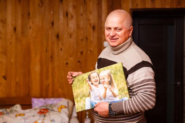 Homme âgé tenant une toile photo dans une maison en bois