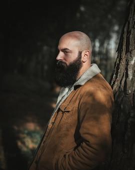 Homme âgé à tête chauve avec une moustache noire dense dans le parc appuyé sur un arbre