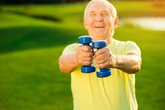 Un homme âgé tient des haltères