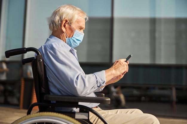 Homme âgé utilisant un fauteuil roulant et se promenant dans la rue de la ville et portant un masque tout en utilisant un smartphone