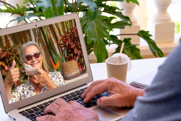 Homme âgé utilisant un ordinateur portable pour un appel vidéo avec une amie souriante absente en raison d'un coronavirus