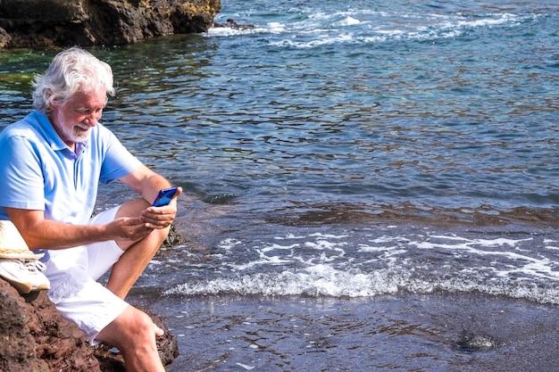 Homme âgé utilisant un téléphone intelligent assis sur les rochers près de l'eau profitant des vacances à la mer