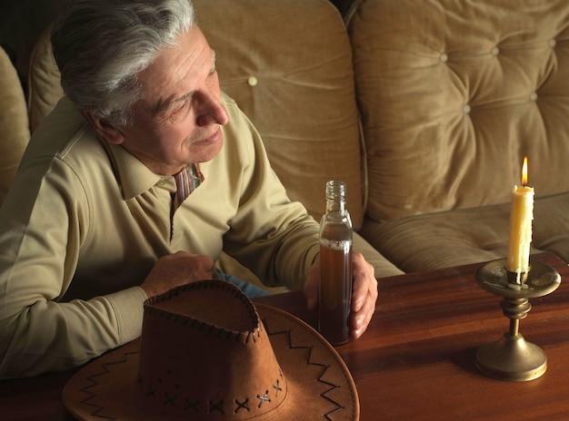 L'homme agréable s'assied tranquillement à sa maison à la table