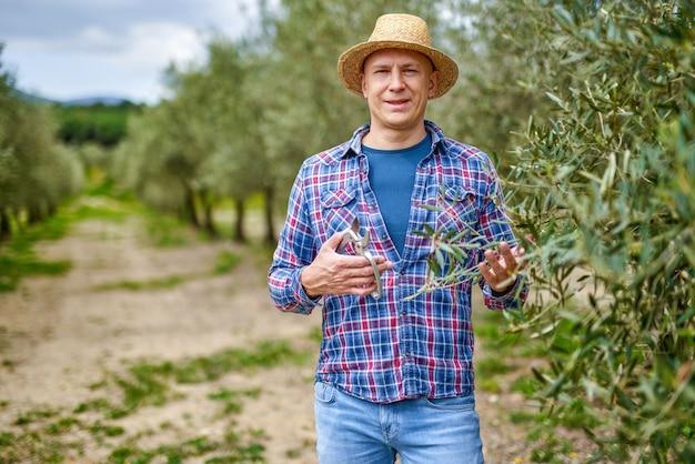 Homme agriculteur avec chapeau de paille à oliveraie.