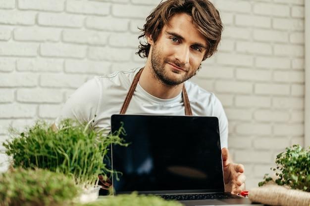 Homme agriculteur montre un écran noir d'ordinateur portable et s'assoit à la table avec des pousses