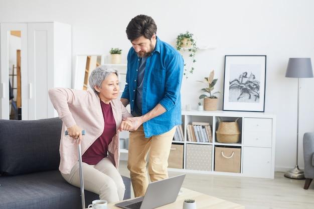 Homme aidant la femme âgée à se lever, il la soutient pendant qu'ils sont dans le salon à la maison