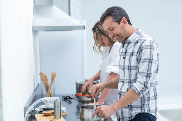 Homme aidant une femme enceinte à préparer un repas dans la cuisine