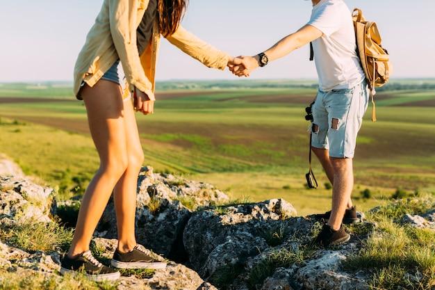 Homme aidant une femme en marchant sur le rocher