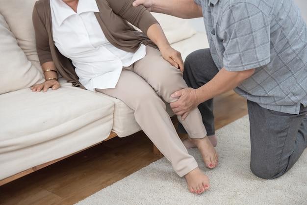 Homme aidant sa femme à s'asseoir sur le canapé
