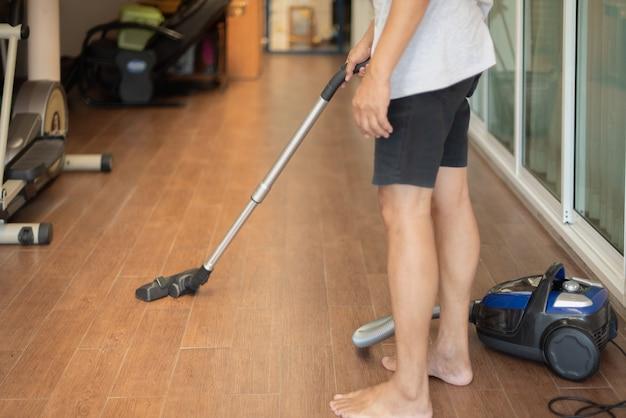 Un homme à l'aide d'un aspirateur à la maison, nettoyage du sol